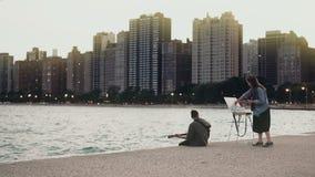 Νέο όμορφο ζεύγος στην ακτή της λίμνης του Μίτσιγκαν, Σικάγο, Αμερική Η γυναίκα σύρει, κιθάρα παιχνιδιού ανδρών απόθεμα βίντεο