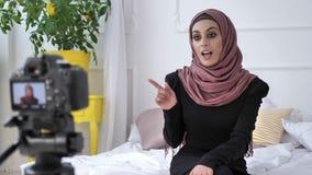 Νέο όμορφο ινδικό κορίτσι στο hijab blogger που μιλά στη κάμερα, χαμογελώντας, gesturing, άσπρο δωμάτιο, εγχώρια άνεση μέσα απόθεμα βίντεο