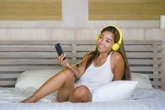 Νέο όμορφο και ευτυχές ασιατικό λατινικό έθνος γυναικών σπουδαστών που αναμιγνύεται άκουσμα στη μουσική με τα ακουστικά στο κρεβά στοκ εικόνα