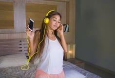 Νέο όμορφο και ευτυχές ασιατικό λατινικό έθνος γυναικών σπουδαστών που αναμιγνύεται άκουσμα στη μουσική με τα ακουστικά στο κρεβά στοκ εικόνες με δικαίωμα ελεύθερης χρήσης