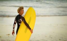 Νέο όμορφο και ευτυχές κορίτσι surfer που περπατά προς τη θάλασσα που φέρνει τον κίτρινο πίνακα κυματωγών έτοιμο για το εύθυμο en στοκ εικόνα με δικαίωμα ελεύθερης χρήσης