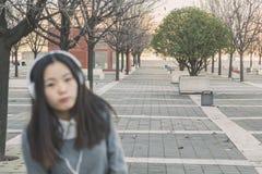 Νέο όμορφο κινεζικό κορίτσι με τα ακουστικά σκόπιμα από την εστίαση Στοκ εικόνα με δικαίωμα ελεύθερης χρήσης