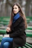 Νέο όμορφο κορίτσι γυαλιά στα μαύρα παλτών μπλε μαντίλι που κάθεται στον πάγκο στο πάρκο πόλεων Ένα κομψό κορίτσι brunette με το  Στοκ Εικόνα