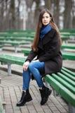 Νέο όμορφο κορίτσι γυαλιά στα μαύρα παλτών μπλε μαντίλι που κάθεται στον πάγκο στο πάρκο πόλεων Ένα κομψό κορίτσι brunette με το  Στοκ Εικόνες