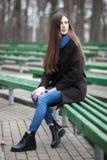 Νέο όμορφο κορίτσι γυαλιά στα μαύρα παλτών μπλε μαντίλι που κάθεται στον πάγκο στο πάρκο πόλεων Ένα κομψό κορίτσι brunette με το  Στοκ εικόνα με δικαίωμα ελεύθερης χρήσης