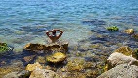 Νέο όμορφο κορίτσι γυναικών που κτενίζει την τρίχα της μεταξύ των πετρών στο κυανό ωκεάνιο νερό θάλασσας στην Ελλάδα απόθεμα βίντεο