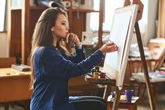 Νέο όμορφο κορίτσι, θηλυκή σκέψη ζωγράφων καλλιτεχνών μια νέα ιδέα έργου τέχνης και έτοιμος να κάνει τον πρώτο brushstroke στοκ φωτογραφία