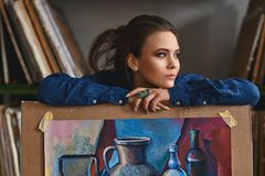 Νέο όμορφο κορίτσι, θηλυκή σκέψη ζωγράφων καλλιτεχνών μια νέα ιδέα έργου τέχνης ή πρόγραμμα που κρατά ένα τελειωμένο έργο τέχνης  Στοκ Φωτογραφίες