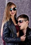 Νέο όμορφο κορίτσι και όμορφος τύπος στα σακάκια και τα γυαλιά ηλίου δέρματος που θέτουν σε μια υψηλή καρέκλα και που φιλούν σε γ Στοκ Φωτογραφία