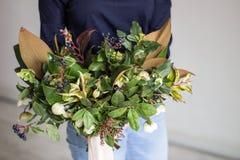 Νέο όμορφο κορίτσι κινηματογραφήσεων σε πρώτο πλάνο που κρατά floral σε ετοιμότητα της Στοκ Φωτογραφίες