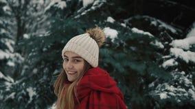 Νέο όμορφο κορίτσι μέσα στα θερμά ενδύματα που περπατούν κοντά στα χριστουγεννιάτικα δέντρα και που εξετάζουν τη κάμερα κίνηση αρ φιλμ μικρού μήκους