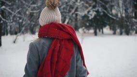 Νέο όμορφο κορίτσι μέσα στα θερμά ενδύματα που τρέχουν κοντά στα χριστουγεννιάτικα δέντρα και που εξετάζουν τη κάμερα σε αργή κίν απόθεμα βίντεο