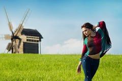 Νέο όμορφο κορίτσι με τη μακριά σκοτεινή τρίχα στον πράσινο τομέα Στοκ φωτογραφία με δικαίωμα ελεύθερης χρήσης