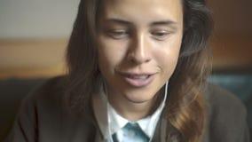 Νέο όμορφο κορίτσι που ακούει τη μουσική στα ακουστικά απόθεμα βίντεο