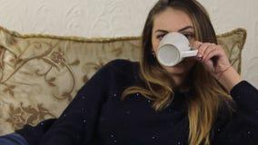 Νέο, όμορφο κορίτσι που βρίσκεται στον καναπέ και τη TV προσοχής και κατανάλωση από μια κούπα ανάβει το μακρινό κατά τρόπο αόριστ απόθεμα βίντεο