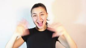 Νέο όμορφο κορίτσι που εξετάζει τη κάμερα που κυματίζει τα όπλα της στο χαιρετισμό απόθεμα βίντεο