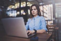 Νέο όμορφο κορίτσι που εργάζεται στο lap-top και που χρησιμοποιεί το κινητό smartphone στον εργασιακό χώρο της στο σύγχρονο κέντρ στοκ εικόνες με δικαίωμα ελεύθερης χρήσης