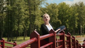Νέο όμορφο κορίτσι που διαβάζει ένα βιβλίο σε ένα πράσινο πάρκο στη γέφυρα ξανθό τρίχωμα απόθεμα βίντεο