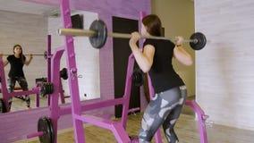 Νέο όμορφο κορίτσι που κάνει τις ασκήσεις με τους αλτήρες στη γυμναστική απόθεμα βίντεο