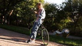 Νέο, όμορφο κορίτσι που κλίνει στο ποδήλατό της στο πάρκο πόλεων Εξετάζοντας την κινητός και smolong, φορώντας φωτεινοί ρόδινος κ απόθεμα βίντεο