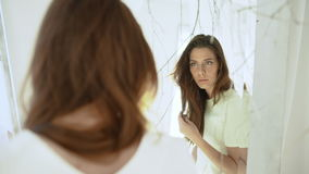Νέο όμορφο κορίτσι που κοιτάζει στον καθρέφτη στο άσπρο ντεκόρ κίνηση αργή απόθεμα βίντεο