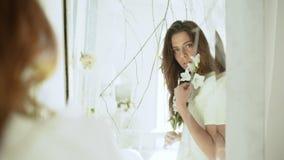 Νέο όμορφο κορίτσι που κοιτάζει στον καθρέφτη στο άσπρο ντεκόρ κίνηση αργή φιλμ μικρού μήκους