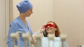 Νέο όμορφο κορίτσι που μιλά με τον οδοντίατρό της στο οδοντικό γραφείο οδοντιατρική φιλμ μικρού μήκους