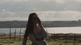 Νέο όμορφο κορίτσι που μιλά στο τηλέφωνο στην επαρχία στο λιβάδι 4K απόθεμα βίντεο