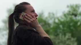 Νέο όμορφο κορίτσι που μιλά στο τηλέφωνο στο πάρκο πόλεων, υπαίθριο απόθεμα βίντεο