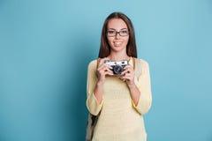 Νέο όμορφο κορίτσι που παίρνει τη φωτογραφία που χρησιμοποιεί το photocamera πέρα από το μπλε υπόβαθρο Στοκ Εικόνες