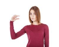 Νέο όμορφο κορίτσι που παρουσιάζει μικρή χειρονομία Στοκ φωτογραφία με δικαίωμα ελεύθερης χρήσης