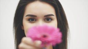 Νέο όμορφο κορίτσι που στέκεται σε ένα άσπρο υπόβαθρο Κατά τη διάρκεια αυτού αύξησε το θολωμένο λουλούδι με τα χέρια του φιλμ μικρού μήκους