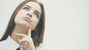 Νέο όμορφο κορίτσι που στέκεται σε ένα άσπρο υπόβαθρο Κατά τη διάρκεια αυτής της σκέψης, φαίνεται προς τα πάνω κυματίζοντας το χέ απόθεμα βίντεο