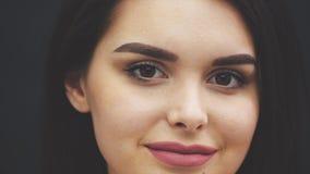 Νέο όμορφο κορίτσι που στέκεται σε ένα μαύρο υπόβαθρο Κατά τη διάρκεια αυτού έχει τα χείλια Το κορίτσι χαμογελά γλυκά απόθεμα βίντεο
