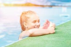 Νέο όμορφο κορίτσι που τρώει το καρπούζι στη λίμνη Στοκ Εικόνες