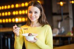 Νέο όμορφο κορίτσι που τρώει το παγωτό στον καφέ Στοκ φωτογραφία με δικαίωμα ελεύθερης χρήσης