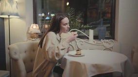 Νέο όμορφο κορίτσι που τρώει φρέσκο cheesecake ή το tiramisu σοκολάτας στόμα-ποτίσματος στο όμορφο εστιατόριο απόθεμα βίντεο