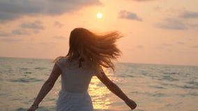 Νέο όμορφο κορίτσι σε ένα άσπρο φόρεμα που περπατά κατά μήκος της παραλίας Ωκεανός φιλμ μικρού μήκους