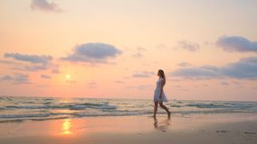 Νέο όμορφο κορίτσι σε ένα άσπρο φόρεμα που περπατά κατά μήκος της παραλίας Ωκεανός απόθεμα βίντεο