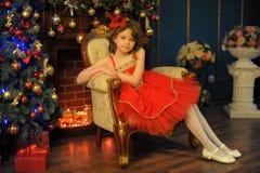 Νέο όμορφο κορίτσι σε ένα κόκκινο φόρεμα δίπλα στην εστία στα Χριστούγεννα στοκ εικόνα με δικαίωμα ελεύθερης χρήσης