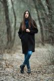 Νέο όμορφο κορίτσι σε ένα μαύρο μπλε μαντίλι παλτών που εξερευνά το δασικό πάρκο φθινοπώρου/άνοιξης Ένα κομψό κορίτσι brunette με Στοκ φωτογραφία με δικαίωμα ελεύθερης χρήσης