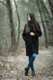 Νέο όμορφο κορίτσι σε ένα μαύρο μπλε μαντίλι παλτών που εξερευνά το δασικό πάρκο φθινοπώρου/άνοιξης Ένα κομψό κορίτσι brunette με Στοκ Εικόνες