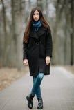 Νέο όμορφο κορίτσι σε ένα μαύρο παλτό και μπλε μαντίλι για έναν περίπατο στο πάρκο φθινοπώρου/άνοιξης Ένα κομψό κορίτσι brunette  Στοκ Εικόνες