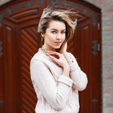 Νέο όμορφο κορίτσι σε ένα πουλόβερ στο υπόβαθρο της πόρτας Στοκ φωτογραφία με δικαίωμα ελεύθερης χρήσης