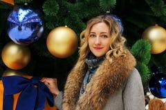 Νέο όμορφο κορίτσι σε ένα χειμερινό παλτό στο υπόβαθρο του χριστουγεννιάτικου δέντρου που διακοσμείται με τις σφαίρες σε ένα εμπο Στοκ Εικόνες