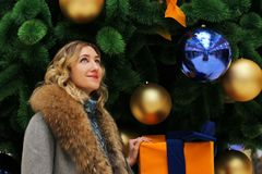 Νέο όμορφο κορίτσι σε ένα χειμερινό παλτό στο υπόβαθρο του χριστουγεννιάτικου δέντρου που διακοσμείται με τις σφαίρες σε ένα εμπο Στοκ φωτογραφία με δικαίωμα ελεύθερης χρήσης