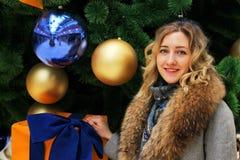 Νέο όμορφο κορίτσι σε ένα χειμερινό παλτό στο υπόβαθρο του χριστουγεννιάτικου δέντρου που διακοσμείται με τις σφαίρες σε ένα εμπο Στοκ εικόνα με δικαίωμα ελεύθερης χρήσης