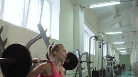 Νέο όμορφο κορίτσι σε μια γυμναστική που κάνει τις ασκήσεις στις στάσεις οκλαδόν με ένα barbell Κατάρτιση στη γυμναστική φιλμ μικρού μήκους