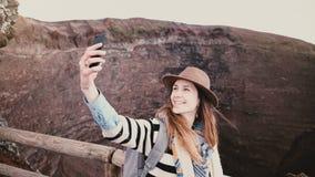 Νέο όμορφο κορίτσι σπουδαστών με το σακίδιο πλάτης που χαμογελά παίρνοντας τη φωτογραφία smartphone selfie στην άκρη του κρατήρα  απόθεμα βίντεο