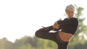 Νέο όμορφο κορίτσι στα μαύρα ενδύματα που κάνουν τη γιόγκα στην ακτή της λίμνης απόθεμα βίντεο